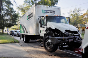 INVESTIGATION: Whitman officers wait for the box truck involved in a morning car crash on Auburn Street as it is towed from the scene Wednesday morning.                                  Photo by Stephanie Spyropoulos.